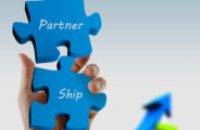 """partnership"" written puzzle pieces in hand"